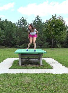 Откровенная молодая девушка в розовых шортах писает в парке - фото #2