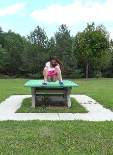 Откровенная молодая девушка в розовых шортах писает в парке - фото #3