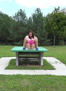 Откровенная молодая девушка в розовых шортах писает в парке - фото #4