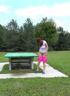Откровенная молодая девушка в розовых шортах писает в парке - фото #14