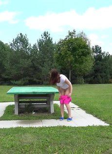 Откровенная молодая девушка в розовых шортах писает в парке - фото #15