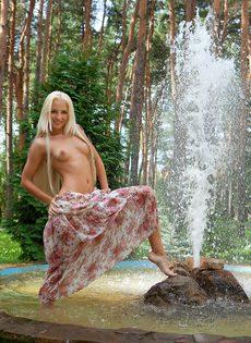 Девушка снимает платье, чтобы намочить стройное молодое тело в фонтане - фото #11