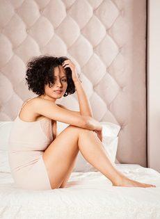 Кудрявая брюнетка обнажилась и разлеглась на просторной кровати - фото #5