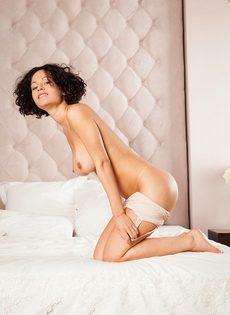 Кудрявая брюнетка обнажилась и разлеглась на просторной кровати - фото #8