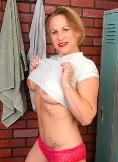 Спортивная женщина с большими сиськами позирует в раздевалке - фото #5