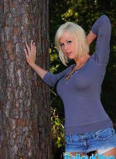 Красивая блондинка показывает свои сиськи в лесу