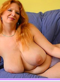 Женщина позирует лежа на диване своими крупными сиськами