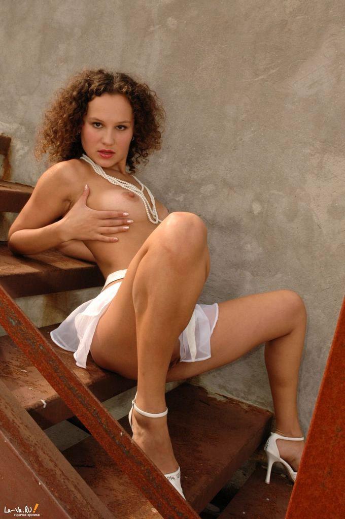 Кудрявая девица шалит с пиздой возле ржавой лестницы
