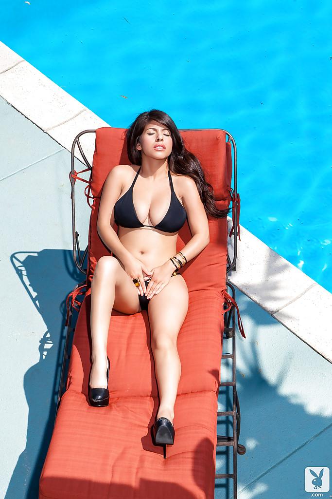 Очаровательная латинка в черном купальнике отдыхает у бассейна