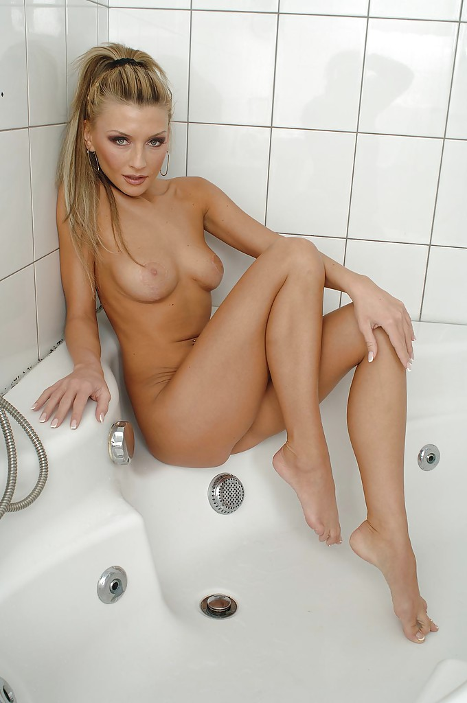 В ванной позирует обворожительная стройная блондинка