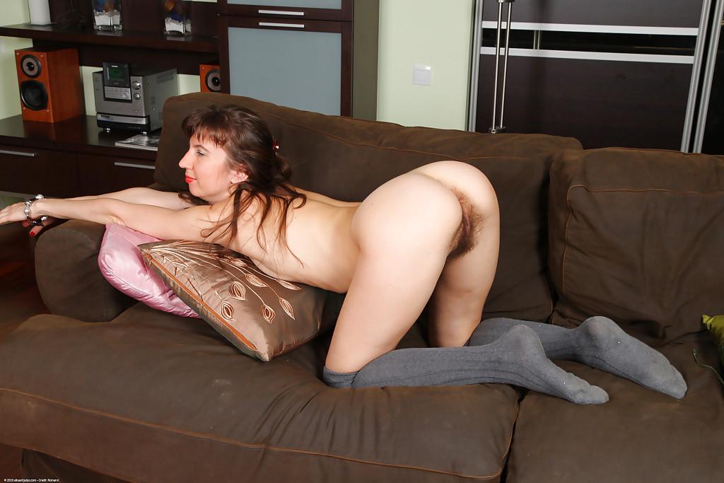 Женщина с волосатой киской присела на мягкий диван