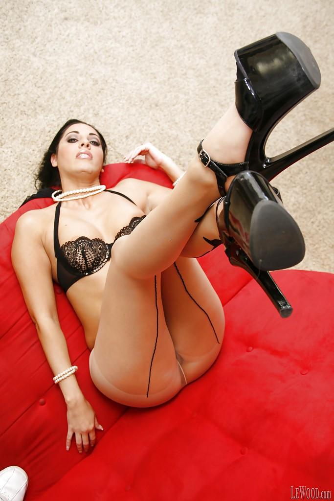 Женщина в колготках снимает нижнее белье и позирует