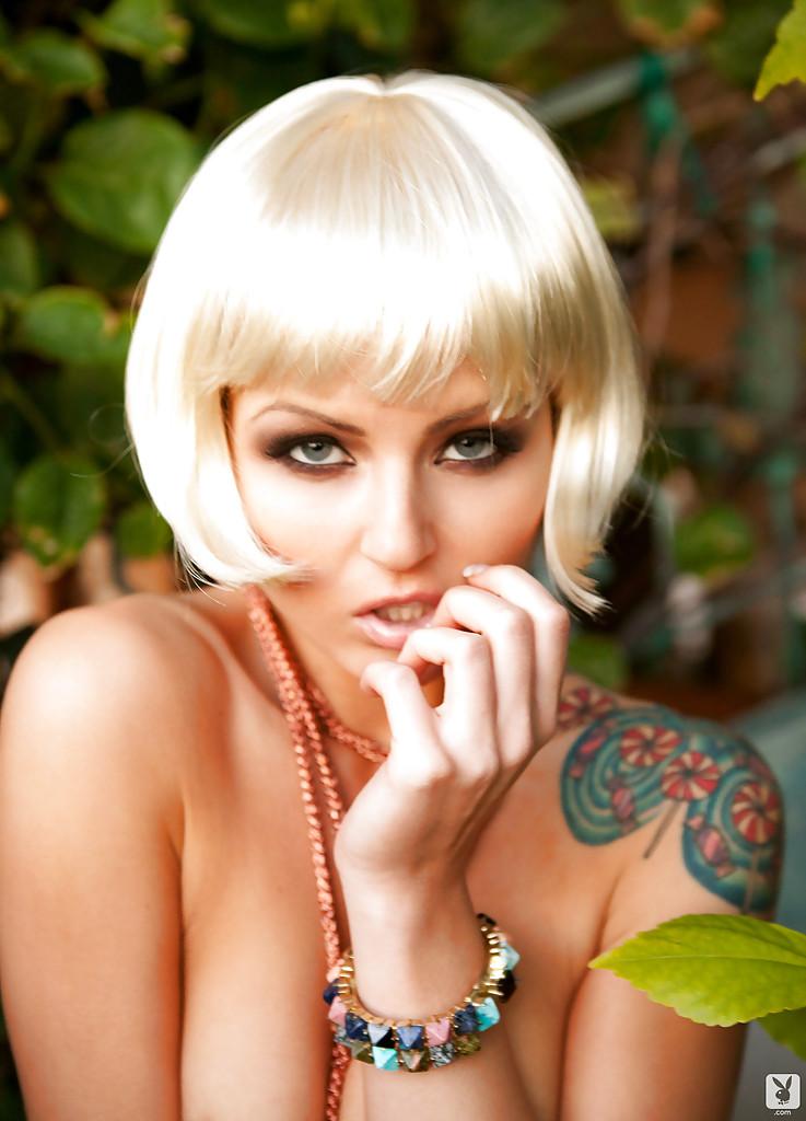 Соблазнительная блондинистая девушка с татуировкой на плече