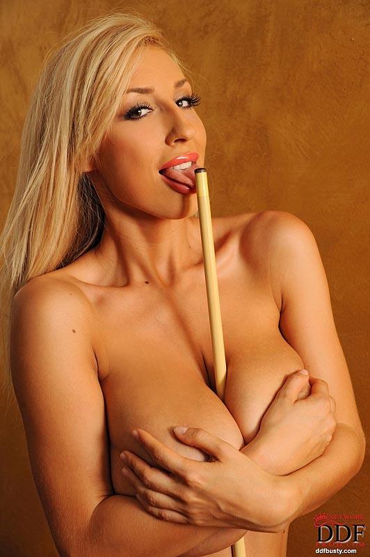 Шикарная блондинка с огромными сиськами позирует возле бильярдного стола
