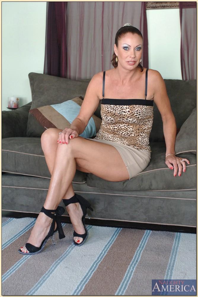 Обнаженная зрелая брюнетка лежит на диване и ждет трахаря