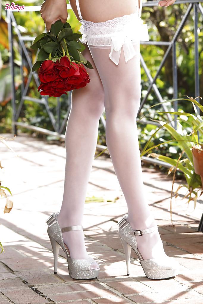 Сладенькая брюнетка в белых чулках позирует с букетом роз