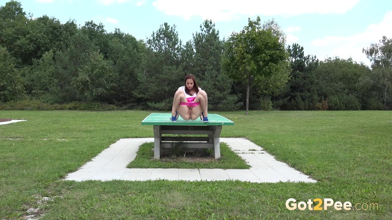 Откровенная молодая девушка в розовых шортах писает в парке