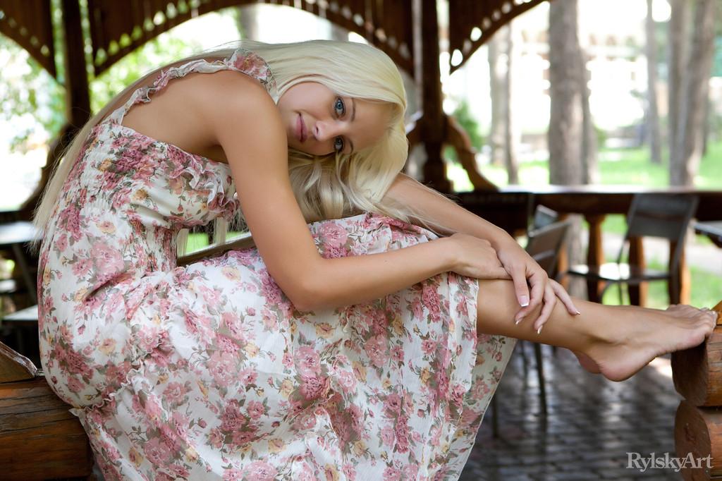Девушка снимает платье, чтобы намочить стройное молодое тело в фонтане