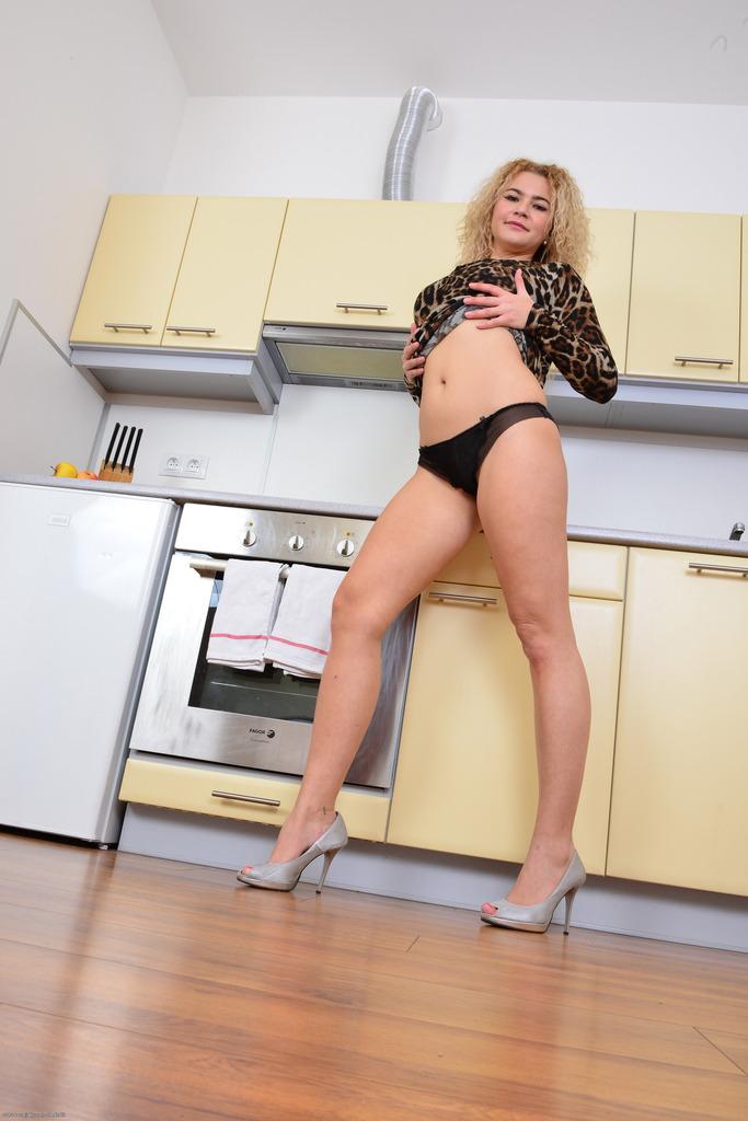 Светловолосая тёлка разлеглась на кухонном столе и показала пизду