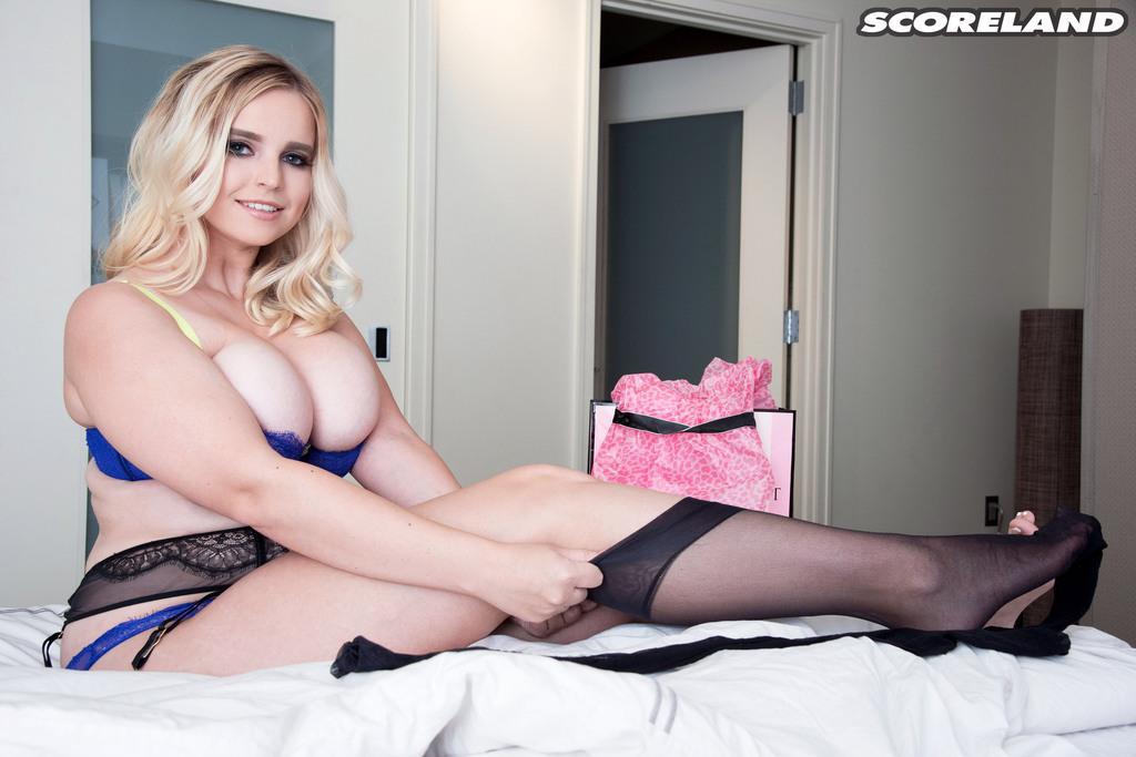 Обаятельная пышная блондинка в сексуальных черных чулочках