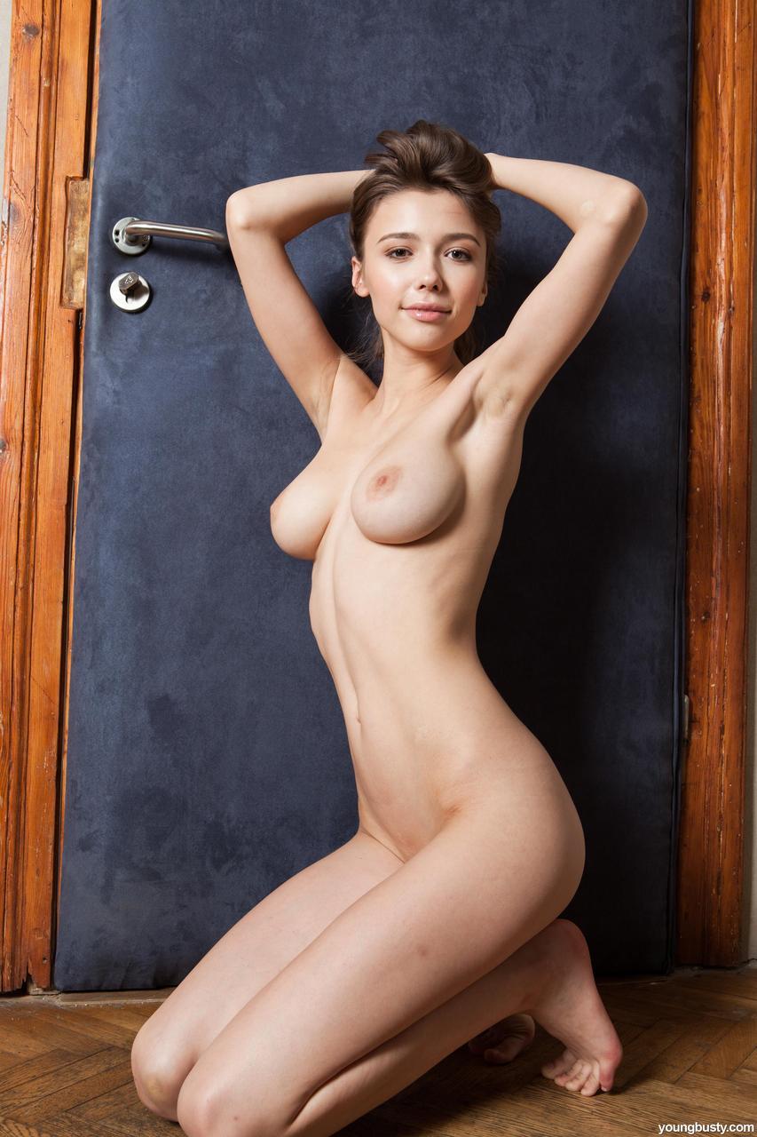 Стройная милашка с красивой упругой грудью позирует у двери