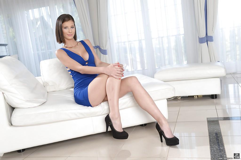 Миниатюрная модель снимает с себя короткое платье синего цвета