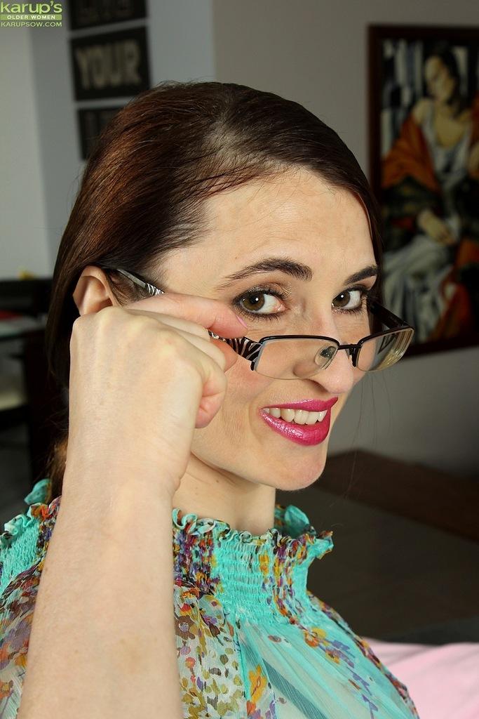 Взрослая женщина в очках демонстрирует промежность на диване