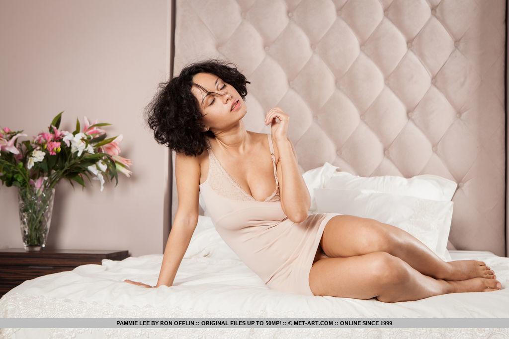 Кудрявая брюнетка обнажилась и разлеглась на просторной кровати