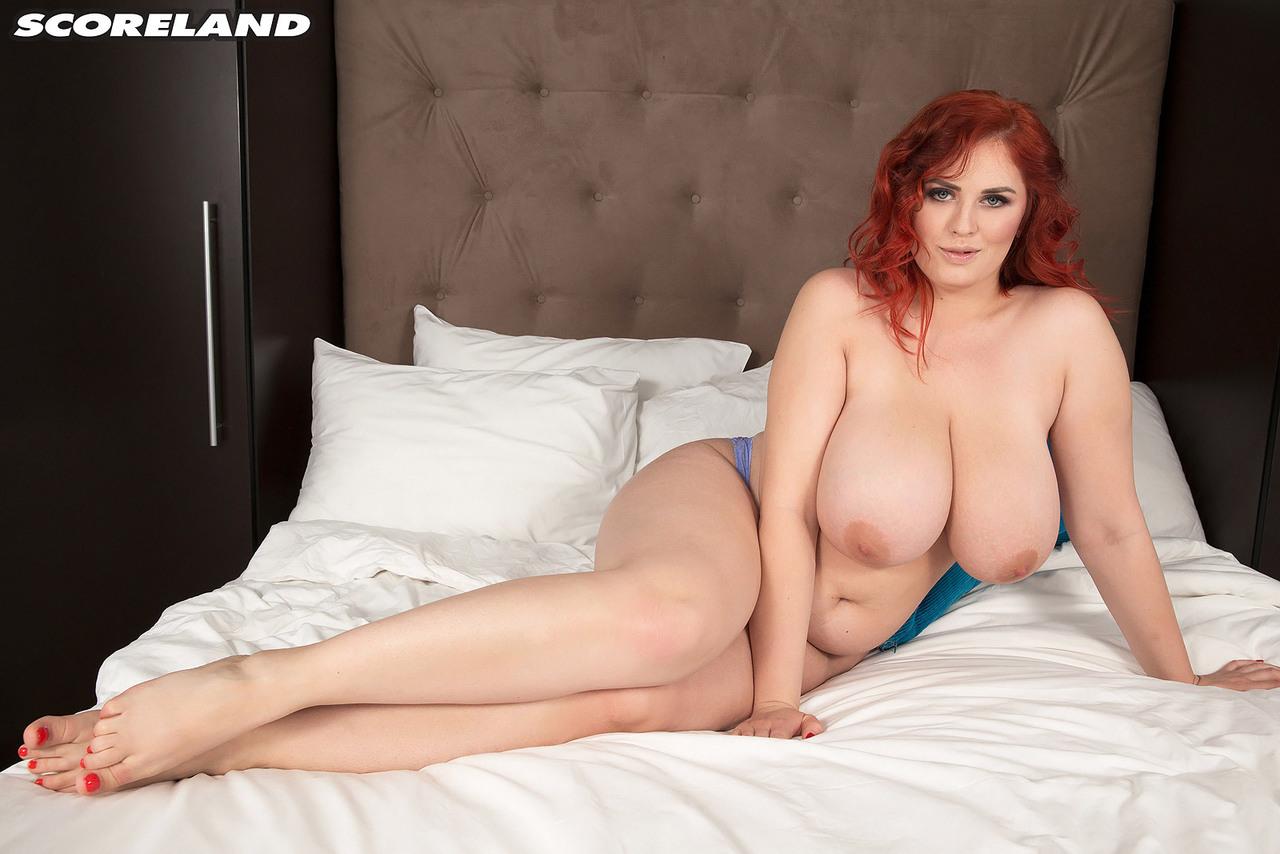 Рыжеволосая толстушка с аппетитными формами лежит на широкой кровати