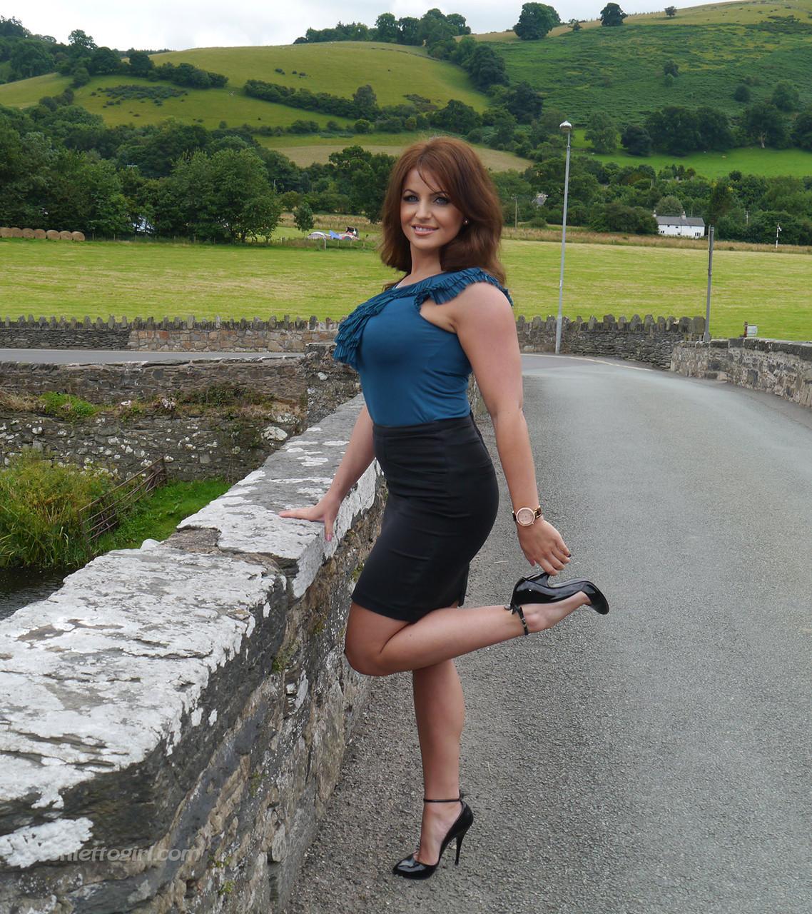 Ухоженная зрелая женщина в юбке и на высоких каблуках