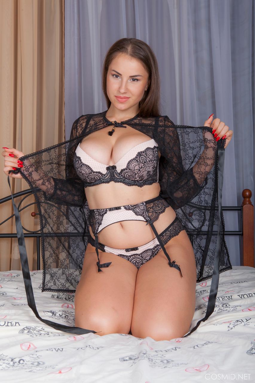 Сексуальная девушка в эротическом наряде позирует в спальне