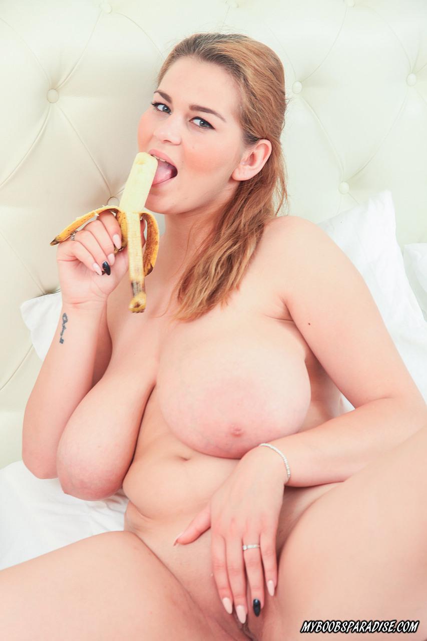 Обнаженная пышногрудая девушка сексуально ест банан