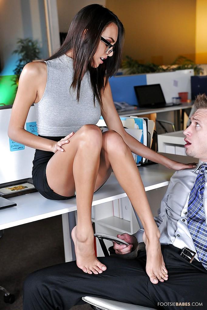 Эффектная брюнетка в очках дрочит ножками пенис сотрудника