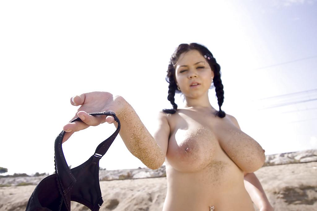 Темноволосая потаскуха хвастается большими дойками на пляже