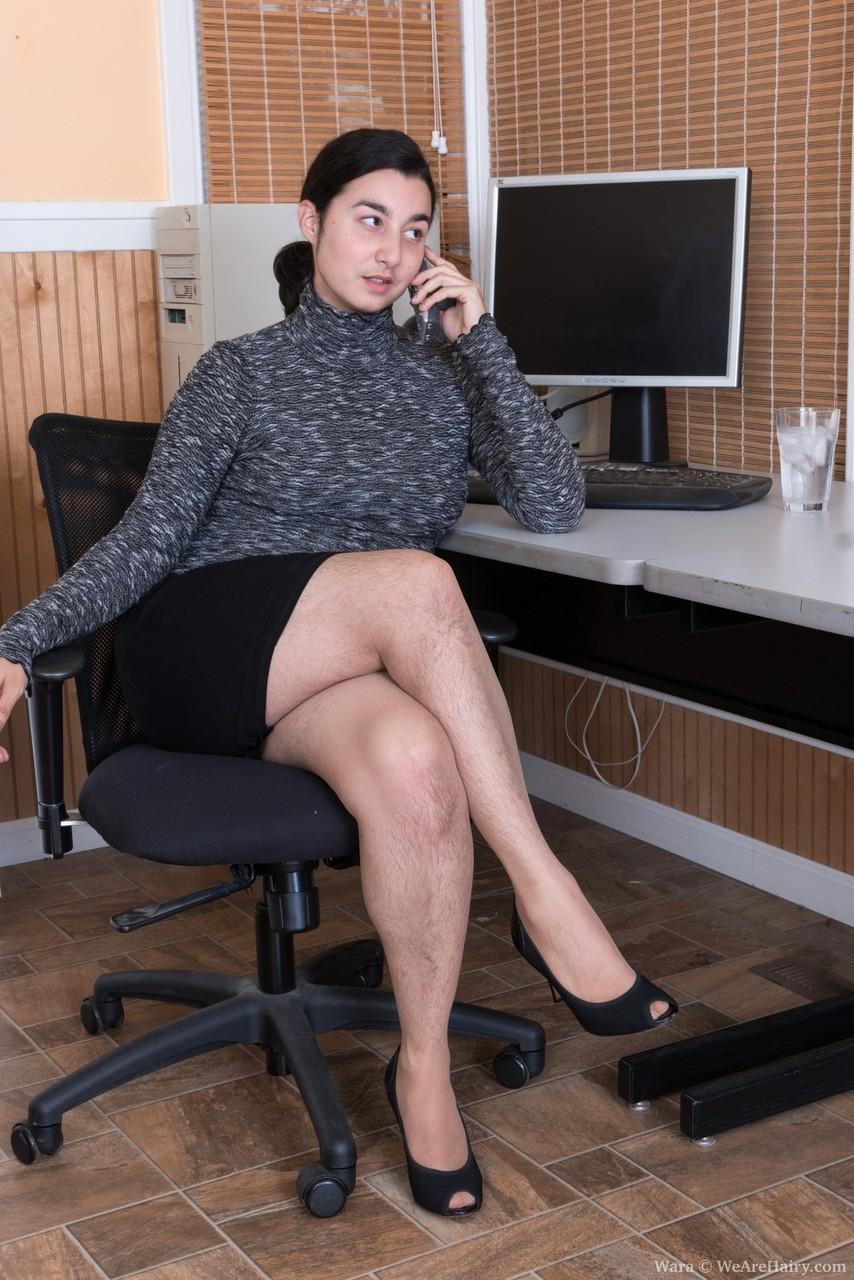 Брюнетка показывает волосатую промежность на рабочем месте