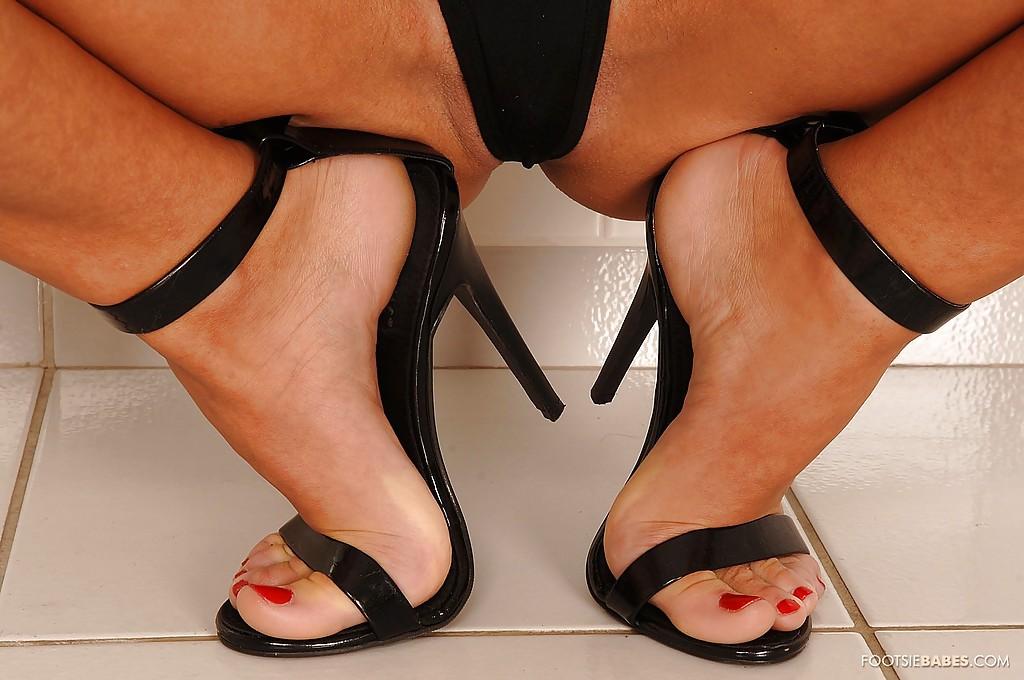 Худенькая развратница демонстрирует ножки на высоких каблуках