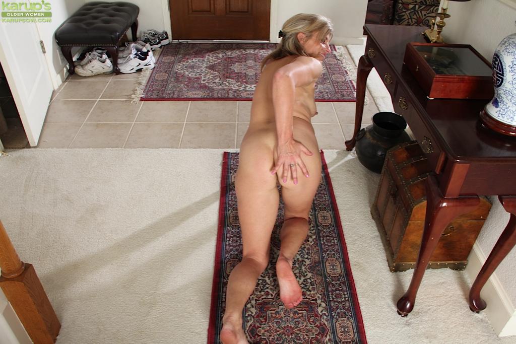 Зрелая баба лежит на полу и стимулирует промежность пальцами