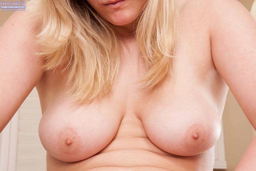 Блондинка стимулирует розовую пилотку на кухонном столе