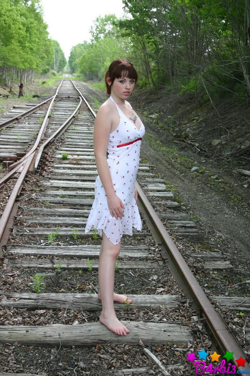 Девушка в белом сарафане фотографируется на железнодорожных путях