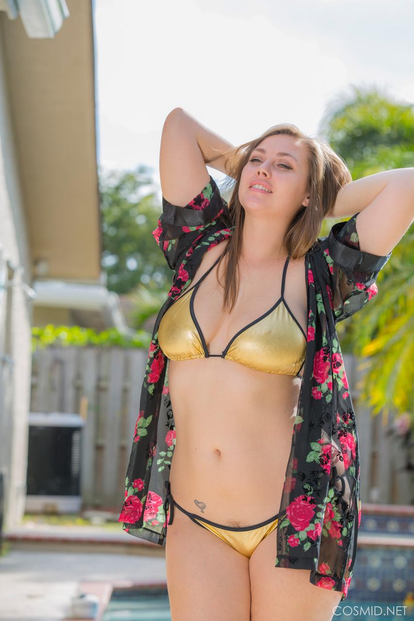 Аппетитная девушка в купальнике позирует на заднем дворе возле бассейна