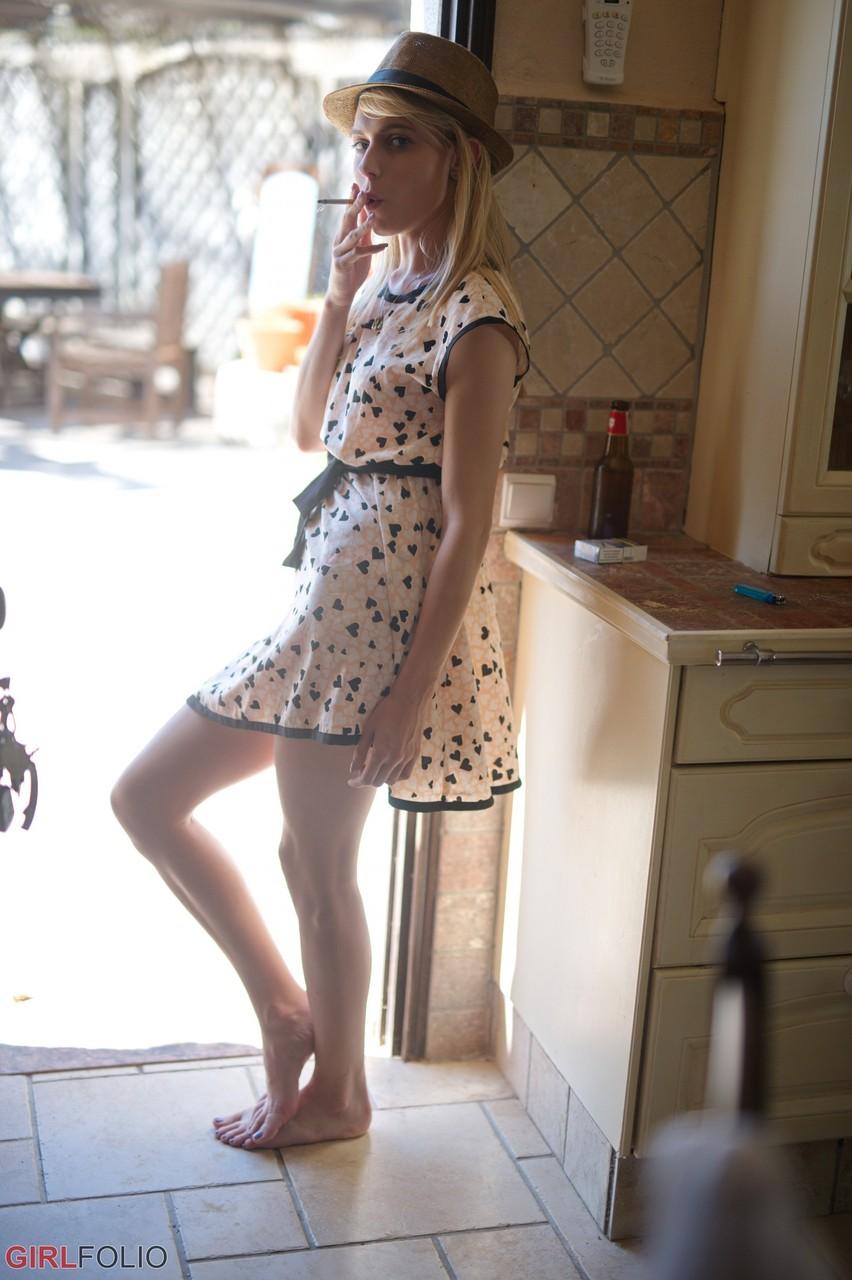 Худенькая блондинка без нижнего белья курит сигарету