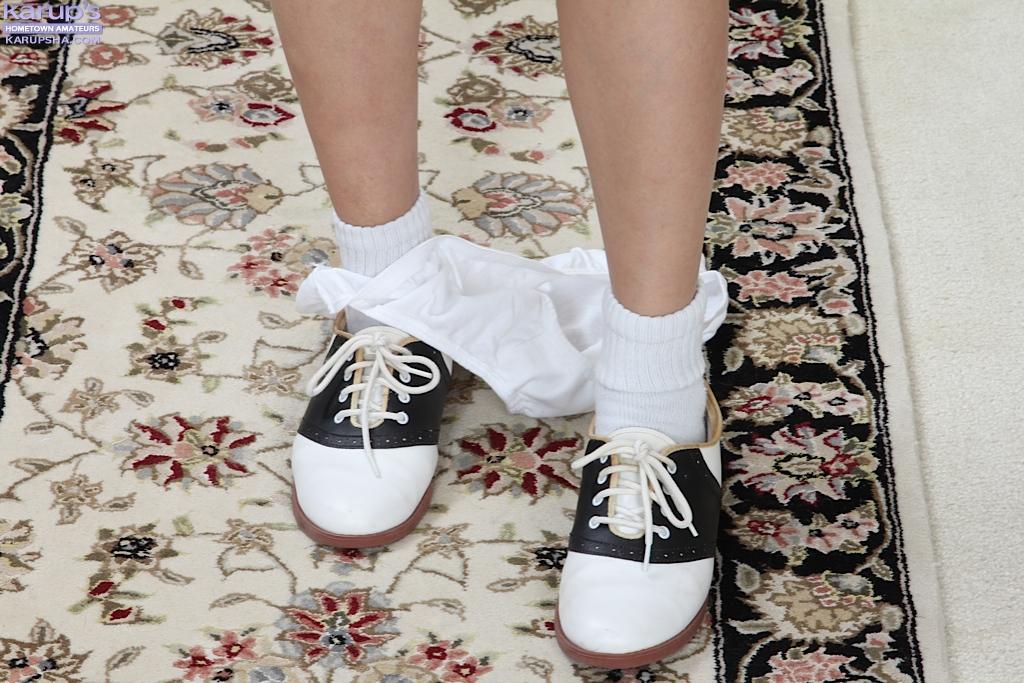 Сучка в белых носках лежит на полу и трогает узенькую киску